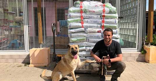 Mann und Hund vor Futtersäcken