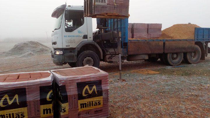 Lkw entlädt Baumaterial für neue Hütten
