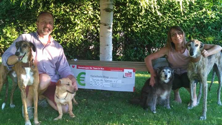 Zwei Tierschützer*innen vom Verein Tierschutz Spanien e.V. mit Scheck und Hunden knien in Wiese