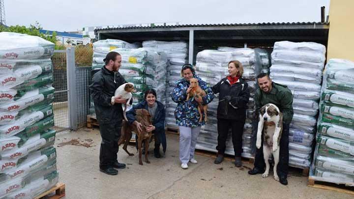 Tierschützer*innen mit Hunden posieren vor Paletten mit Hundefutter